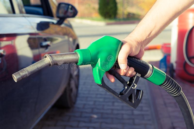De holdingsbenzinepomp van de mensenhand in een benzinestation stock afbeelding