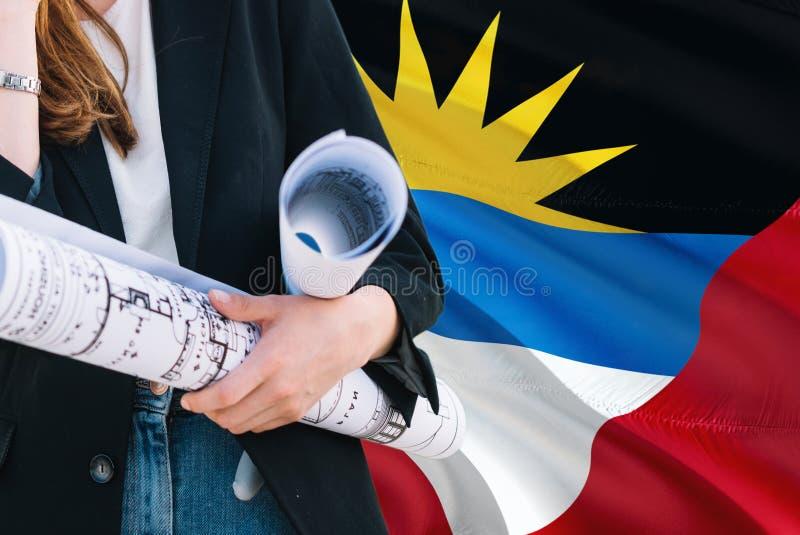 De holdingsblauwdruk van de architectenvrouw tegen Antigua en golvende de vlagachtergrond van Barbuda Bouw en architectuurconcept stock afbeeldingen