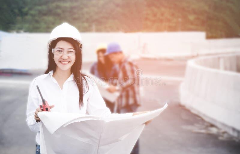 De holdingsblauwdruk van de ingenieurs Aziatische vrouw met radio voor de controle van de arbeidersveiligheid bij de industrie va royalty-vrije stock foto