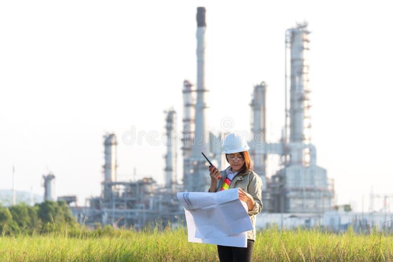 De holdingsblauwdruk van de ingenieursvrouw met radio voor de controle van de arbeidersveiligheid bij elektrische centraleenergie royalty-vrije stock fotografie