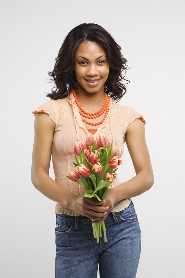 De holdingsbloemen van de vrouw. stock afbeelding