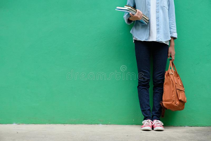 De holdingsboeken en schooltas die van het studentenmeisje zich over groene wa bevinden stock afbeeldingen