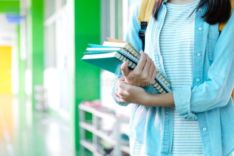 De holdingsboeken van het studentenmeisje bij de achtergrond van de schoolcampus, educatio stock foto's