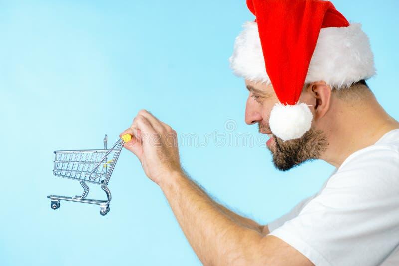 De holdingsboodschappenwagentje van de kerstmanmens stock fotografie