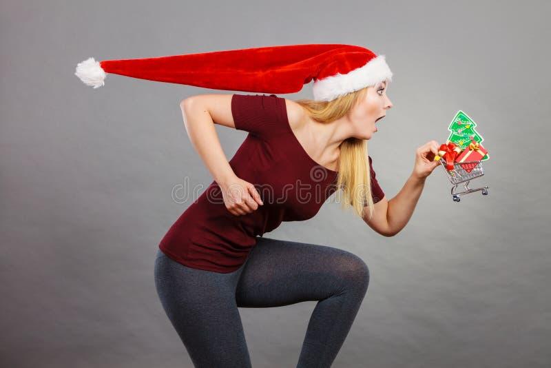 De holdingsboodschappenwagentje van de kerstmanvrouw met Kerstmisgiften stock foto