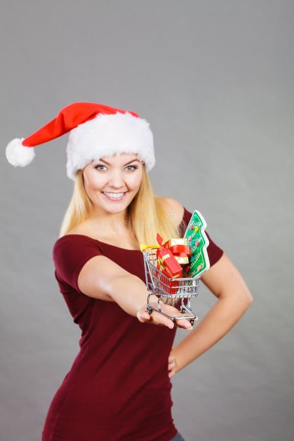 De holdingsboodschappenwagentje van de kerstmanvrouw met Kerstmisgiften stock afbeelding