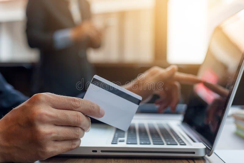 De holdingscreditcard van de zakenman en het gebruiken van laptop royalty-vrije stock foto