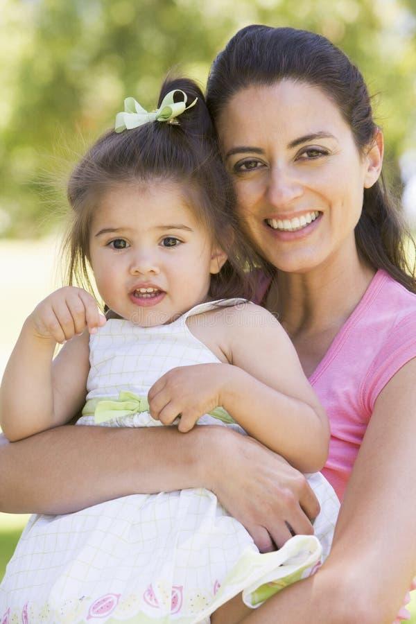 De holdingsdochter die van de moeder in openlucht glimlacht stock foto
