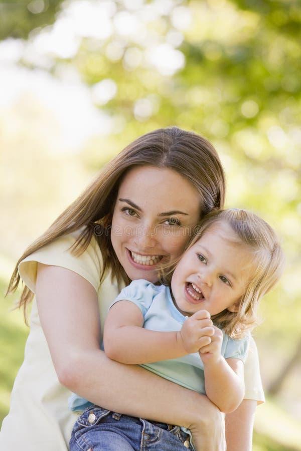 De holdingsdochter die van de moeder in openlucht glimlacht royalty-vrije stock afbeeldingen