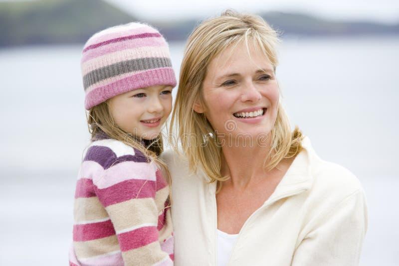 De holdingsdochter van de moeder bij strand het glimlachen royalty-vrije stock foto