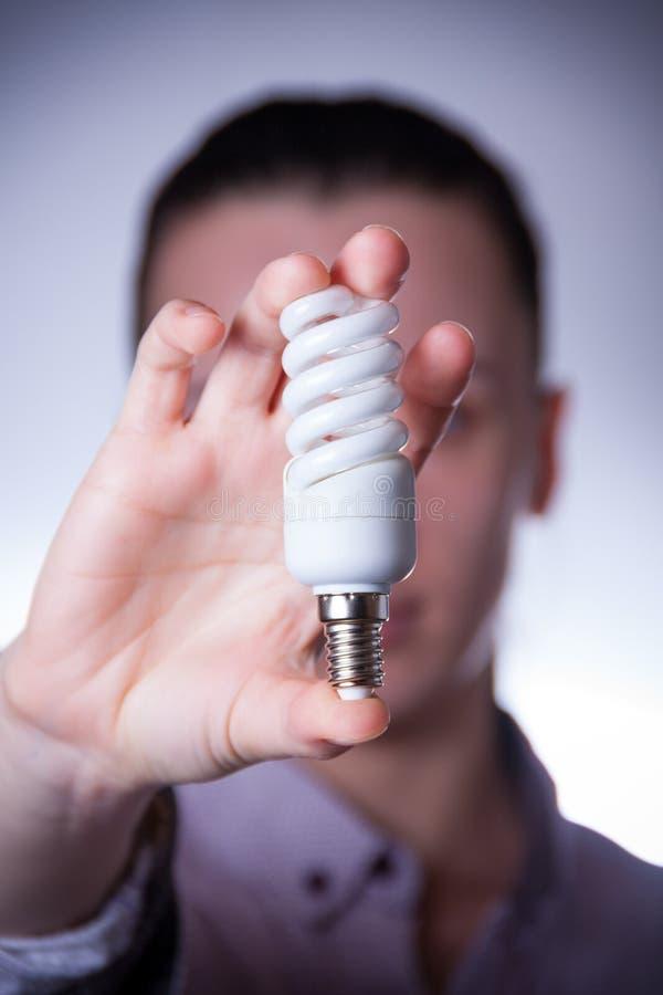 De holdingsenergie van de persoon - besparingslamp royalty-vrije stock afbeelding