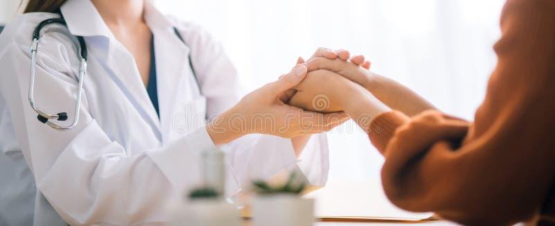De holdingshand van de artsenvrouw voor het geruststellen van haar vrouwelijke patiënt stock fotografie