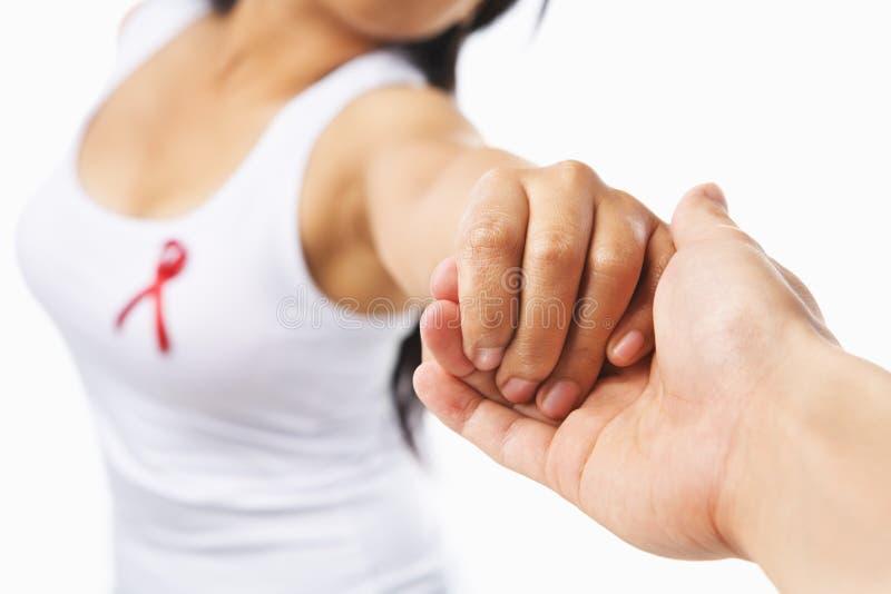 De holdingshand van de vrouw om de oorzaak van AIDS te steunen stock afbeelding