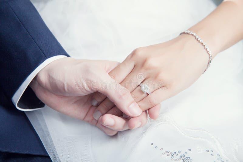 De holdingshand van het huwelijkspaar met diamantring royalty-vrije stock afbeeldingen