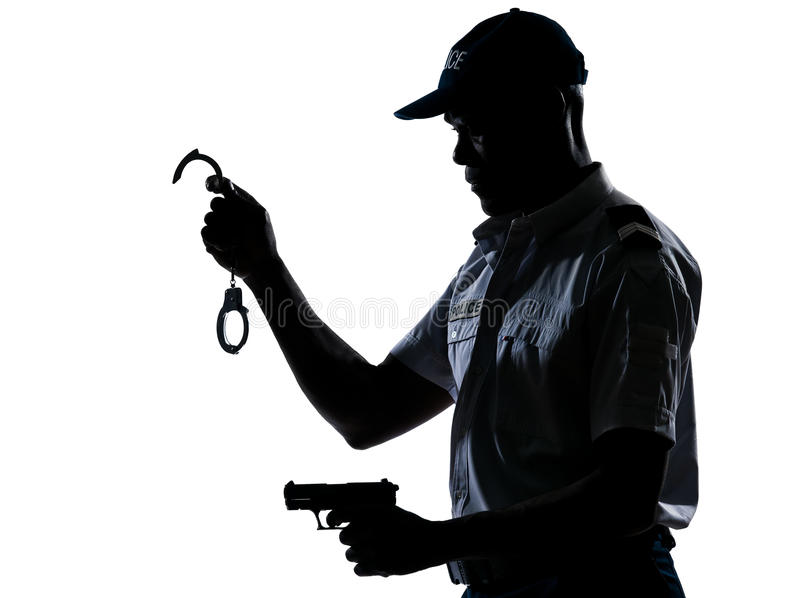 De holdingshandcuffs en pistool van de politieagent stock afbeeldingen