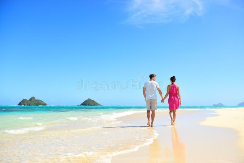 De holdingshanden die van het strandpaar op Hawaï lopen stock afbeelding