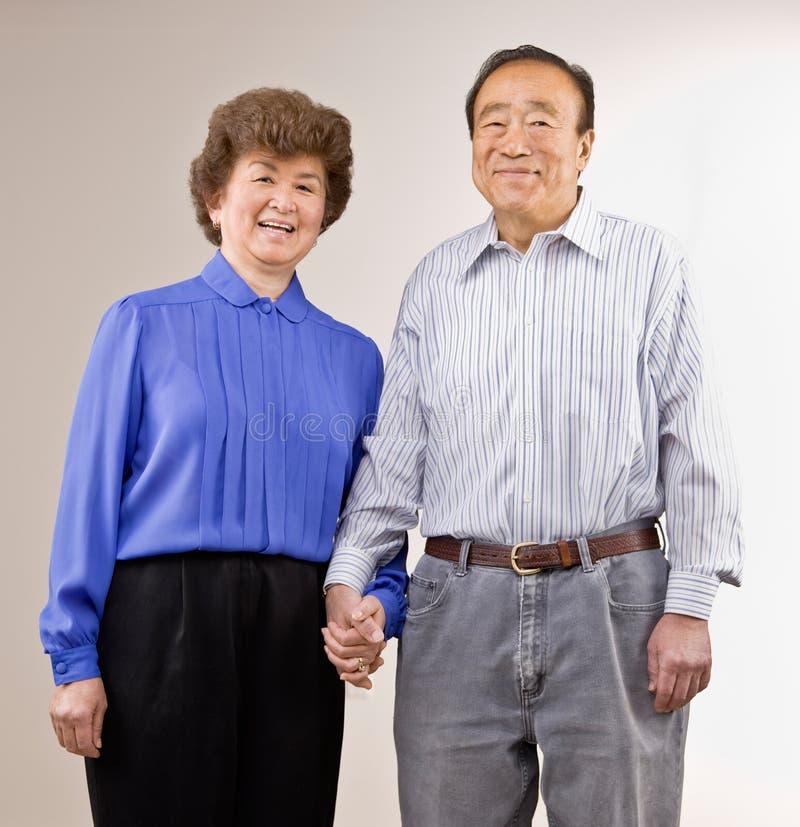 De holdingshanden van het echtpaar stock afbeeldingen