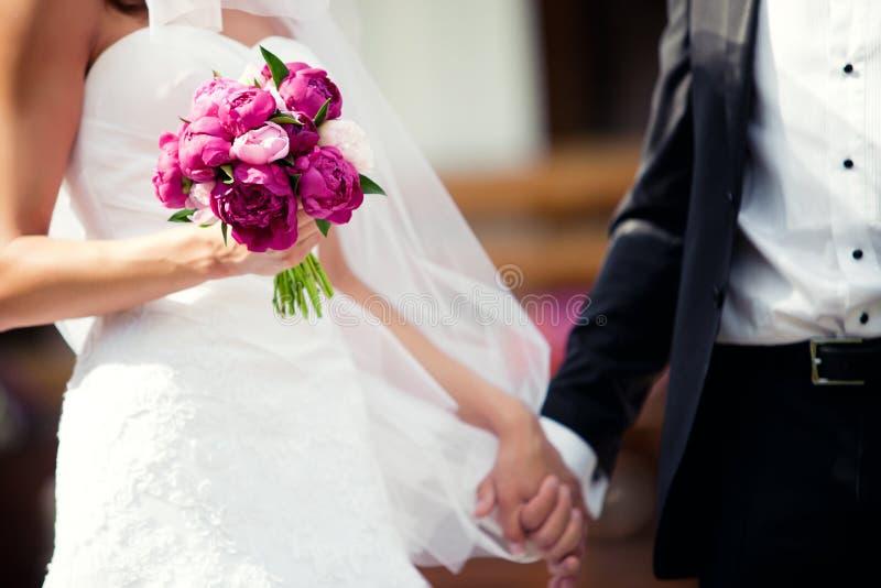 De holdingshanden van het huwelijkspaar stock fotografie