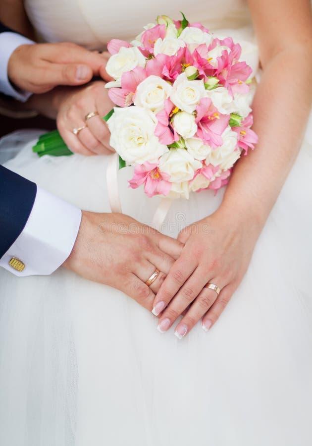 De holdingshanden van het huwelijkspaar met een boeket van bloemen royalty-vrije stock foto's