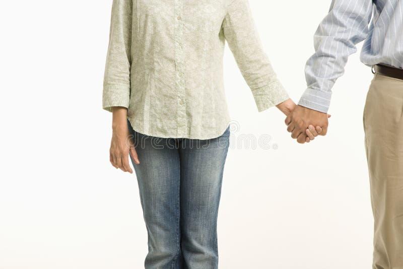 De holdingshanden van het paar. stock foto