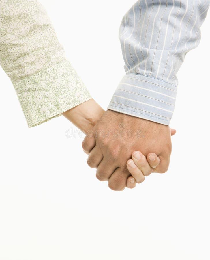 De holdingshanden van het paar. stock foto's