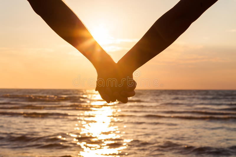 De holdingshanden van het paar bij strand royalty-vrije stock fotografie
