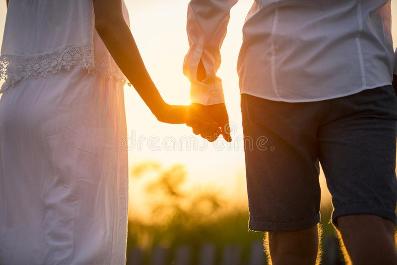 De holdingshanden van het paar bij zonsondergang royalty-vrije stock afbeelding