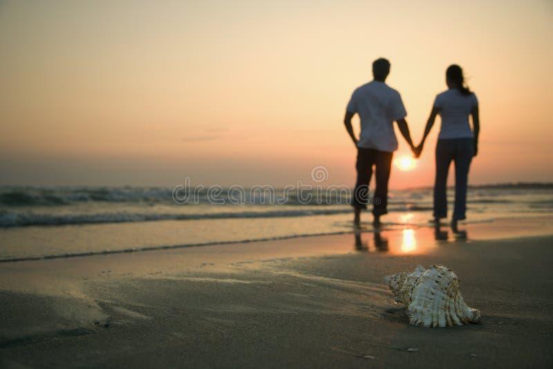 De holdingshanden van het paar op strand. royalty-vrije stock afbeeldingen