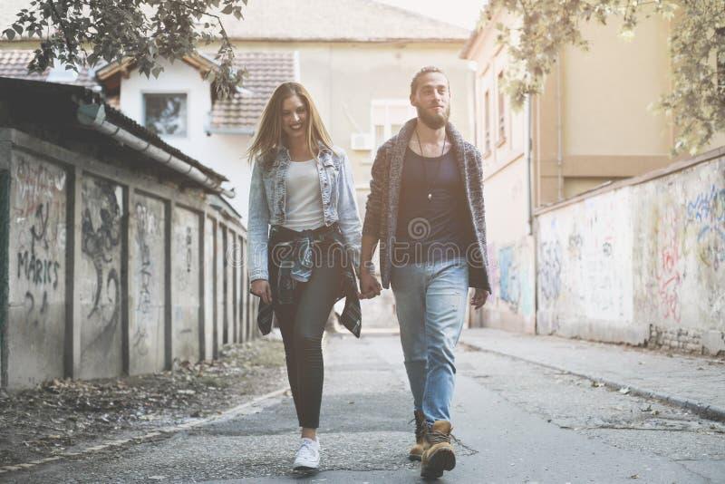 De holdingshanden van het paar in openlucht Het jonge paar waling op de straat stock fotografie