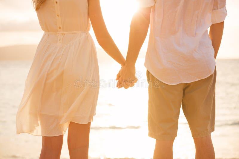 De holdingshanden van het paarpaar bij zonsondergang op strand stock fotografie