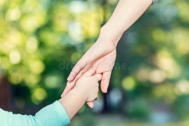 De holdingshanden van het peutermeisje met haar moeder royalty-vrije stock foto