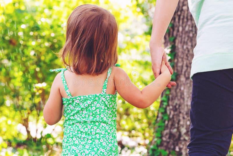 De holdingshanden van het peutermeisje met haar moeder stock foto