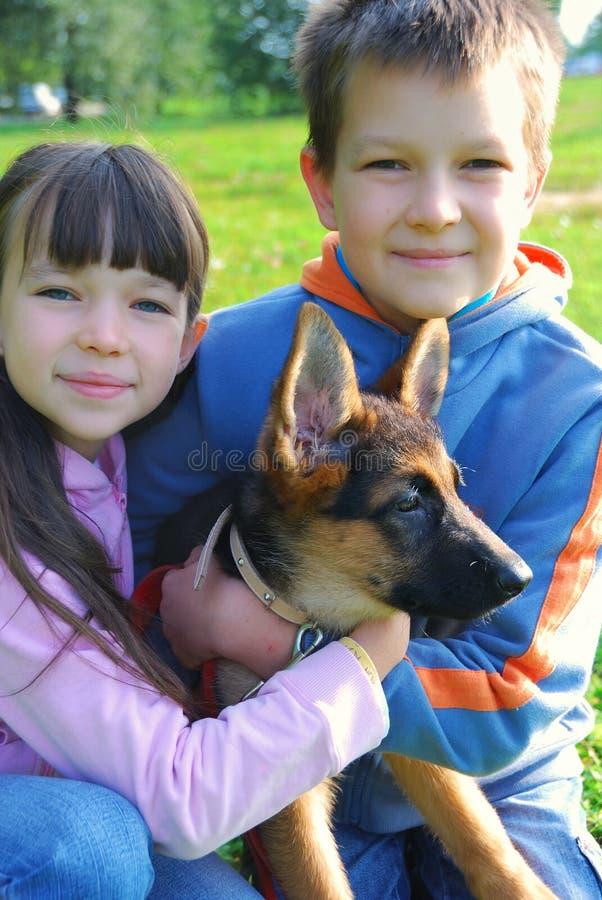 De holdingshond van de jongen en van het meisje stock foto's