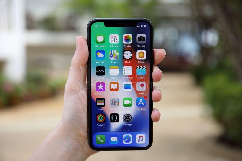 De holdingsiphone X van de vrouwenhand met IOS 11 op het scherm stock fotografie