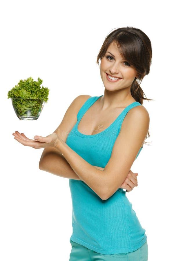 De holdingskom van de vrouw met salade stock afbeeldingen