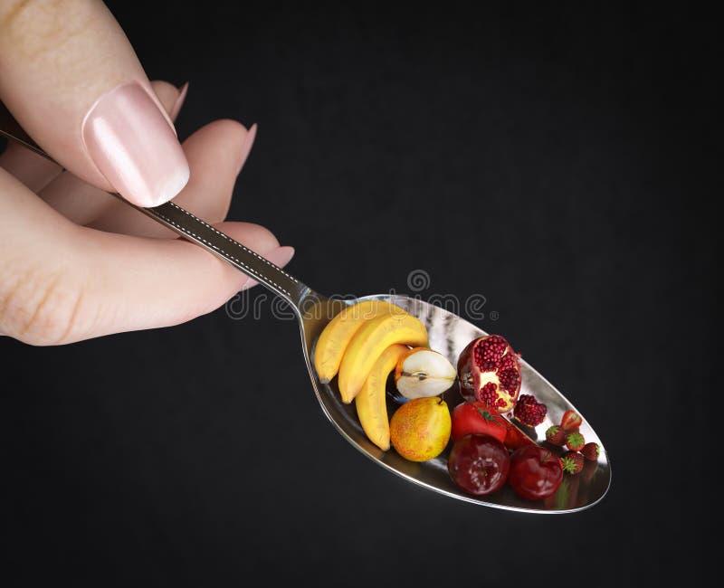 De holdingslepel van de vrouwenhand met vruchten op isolate zwarte de fotoclose-up van het dieetconcept stock afbeeldingen