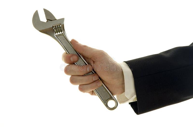 De holdingsmoersleutel van de zakenman stock fotografie