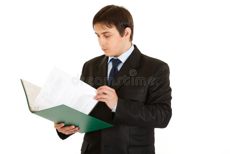 De holdingsomslag van de zakenman en het controleren van documenten stock afbeelding