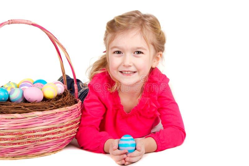 De holdingspaasei van het kind met Pasen mand stock afbeeldingen