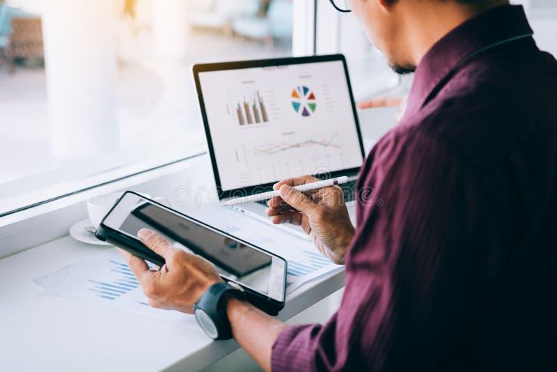 De holdingspen die van de investeerdersmens tablet richten aan het analyseren van grafieken op computerlaptop in bureau royalty-vrije stock afbeelding