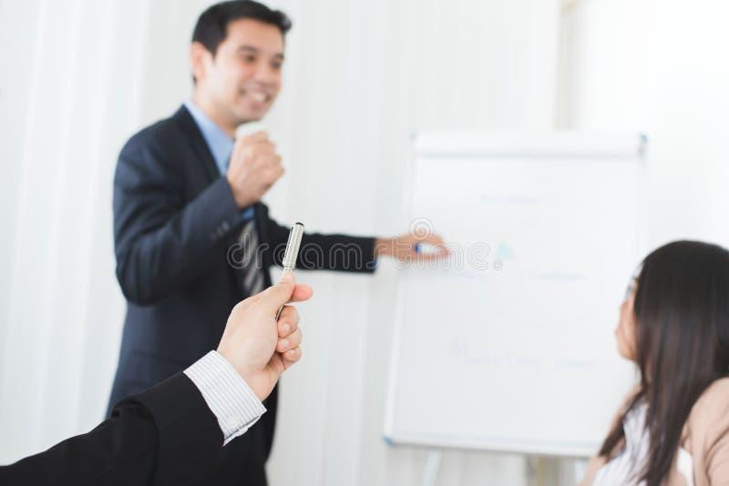 De holdingspen van de zakenmanhand en het richten aan krachtige vergadering le royalty-vrije stock afbeelding