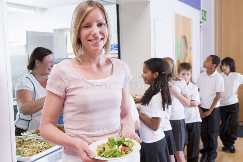 De holdingsplaat van de leraar van lunch in schoolcafetaria royalty-vrije stock foto's