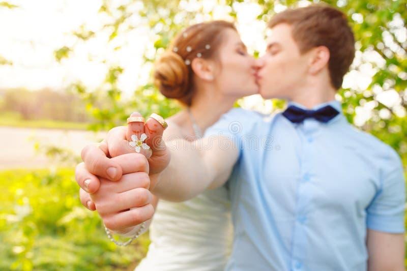 De holdingsringen van de bruid & van de bruidegom stock foto's