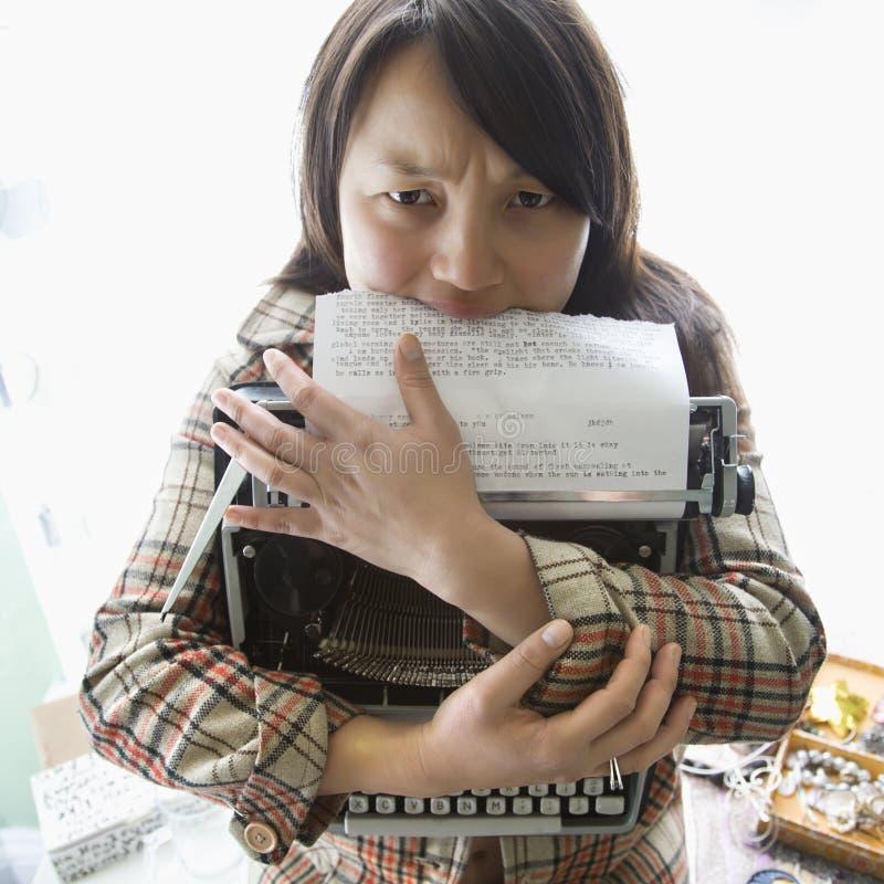 De holdingsschrijfmachine van de vrouw. stock afbeelding