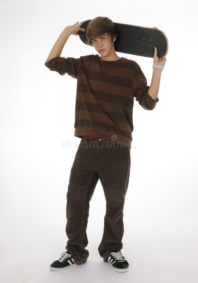 De holdingsskateboard van de tiener achter hoofd stock afbeeldingen