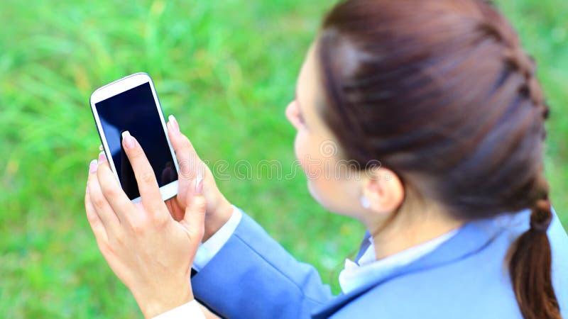 De holdingssmartphone van de vrouwenhand tegen de lente royalty-vrije stock foto