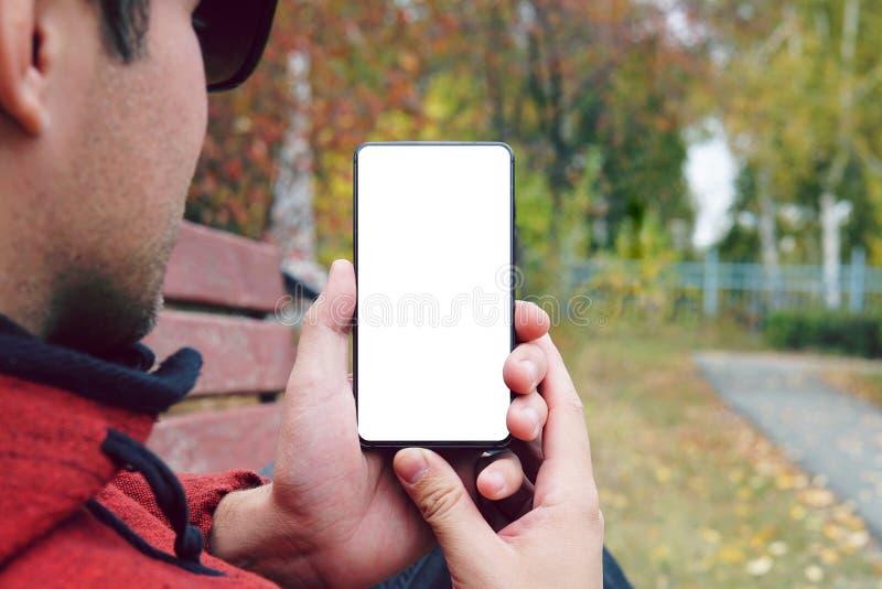 De holdingssmartphone van de jonge mensenhand met het witte scherm in openlucht tegen de herfststoep de kerel bekijkt het scherm  royalty-vrije stock afbeelding
