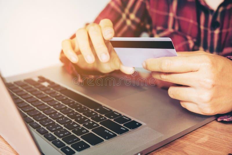 De holdingssmartphone van de mensenhand en creditcard die online bankwezen doen stock foto