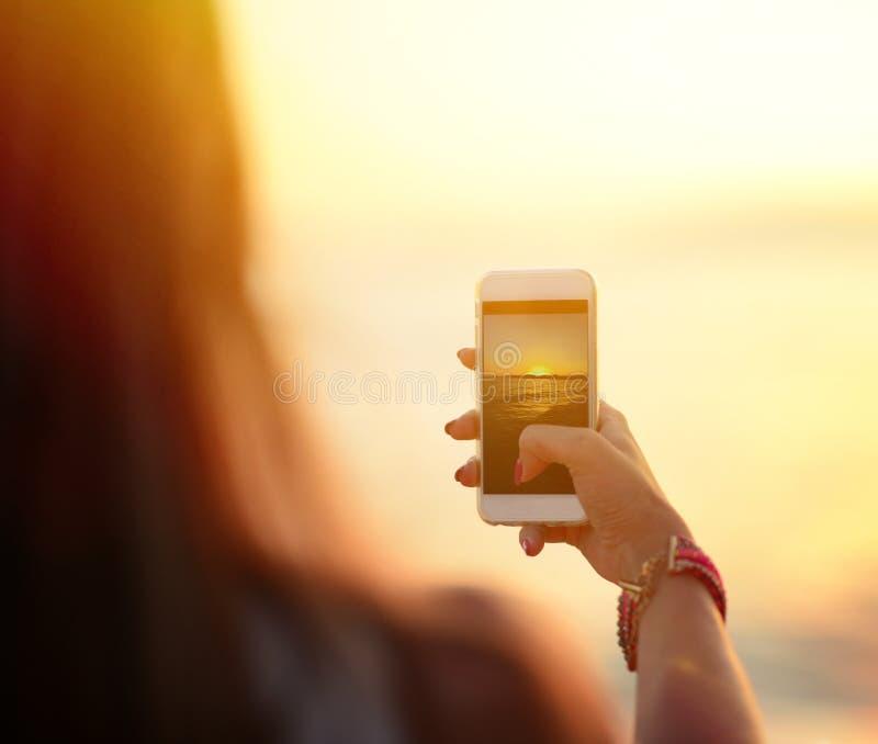De holdingssmartphone van de toeristenhand en het nemen van foto van mooie strandzonsondergang stock afbeeldingen