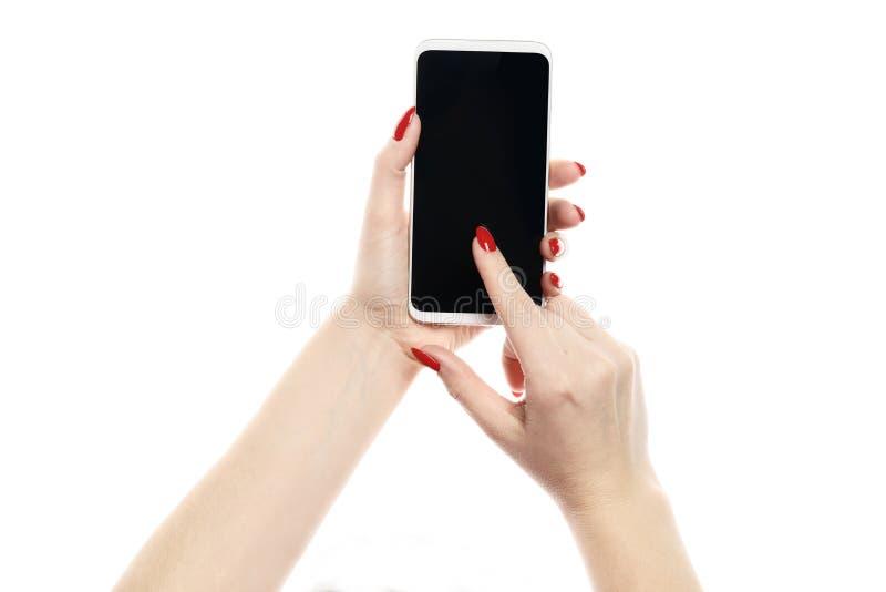 De holdingssmartphone van de vrouwenhand op witte achtergrond wordt geïsoleerd die Rode manicure stock fotografie